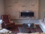 Stone fireplace wall with floating shelves & Horizontal gas fireplace.